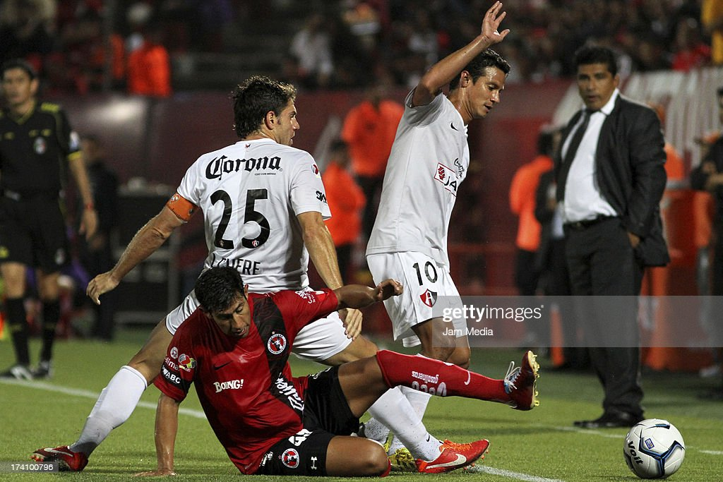 Cristian Pellerano of Tijuana struggles for the ball with <a gi-track='captionPersonalityLinkClicked' href=/galleries/search?phrase=Jose+Luis+Chavez&family=editorial&specificpeople=5481885 ng-click='$event.stopPropagation()'>Jose Luis Chavez</a> of Atlas during the Apertura 2013 Liga Bancomer MX at Caliente Stadium on july 19, 2013 in Tijuana, Mexico.