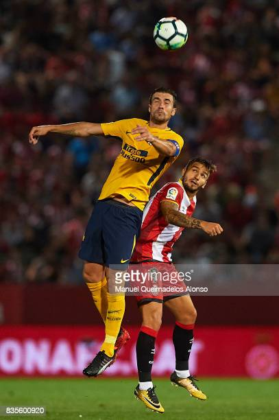 Cristian Portugues of Girona competes for the ball with Gabi of Atletico de Madrid during the La Liga match between Girona and Atletico Madrid at...
