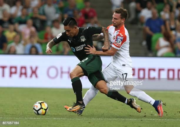 Cristian Ramirez of FC Krasnodar is challenged by Nikolay Dimitrov of FC Ural Ekaterinburg during the Russian Premier League match between FC...