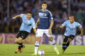 Cristian Rodriguez and Egidio Arevalo Rios of Uruguay vies for the ball with Erik Lamela of Argentina during a match between Uruguay and Argentina as...