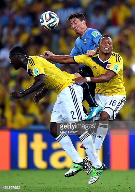 Cristian Rodriguez of Uruguay competes for the ball against Cristian Zapata and Juan Camilo Zuniga of Colombia during the 2014 FIFA World Cup Brazil...