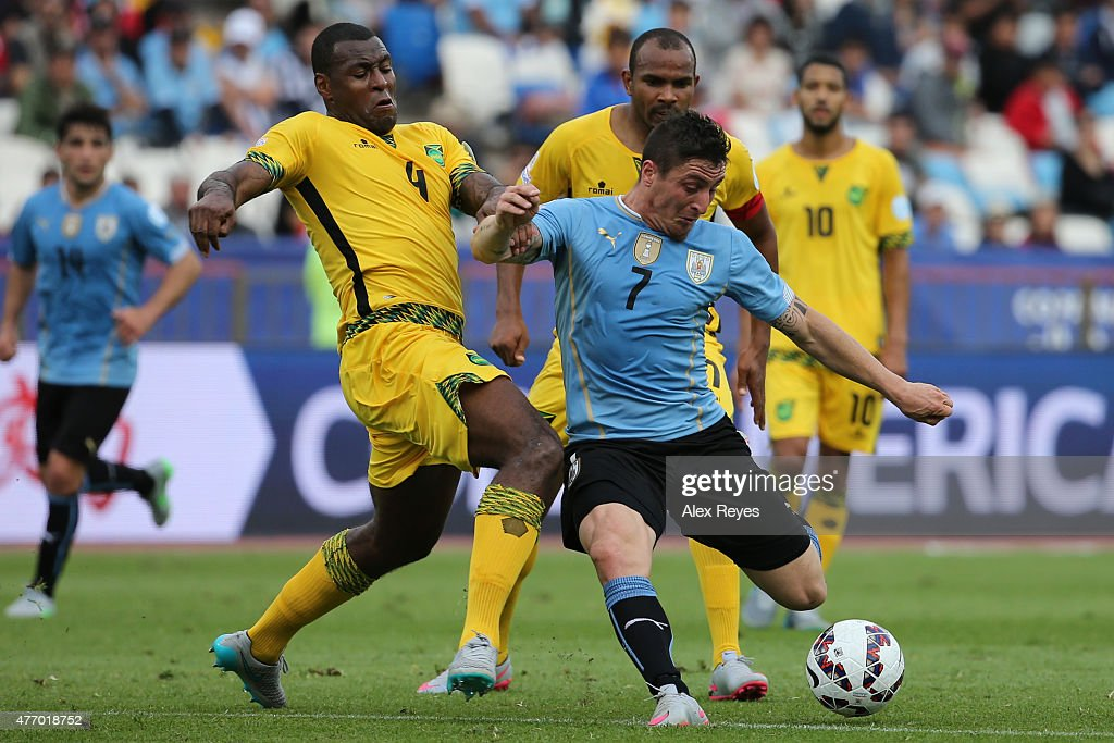 Cristian Rodriguez of Uruguay fights for the ball with <a gi-track='captionPersonalityLinkClicked' href=/galleries/search?phrase=Wes+Morgan+-+Soccer+Player&family=editorial&specificpeople=13491493 ng-click='$event.stopPropagation()'>Wes Morgan</a> of Jamaica during the 2015 Copa America Chile Group B match between Uruguay and Jamaica at Regional Calvo y Bascuñan Stadium on June 13, 2015 in Antofagasta, Chile.