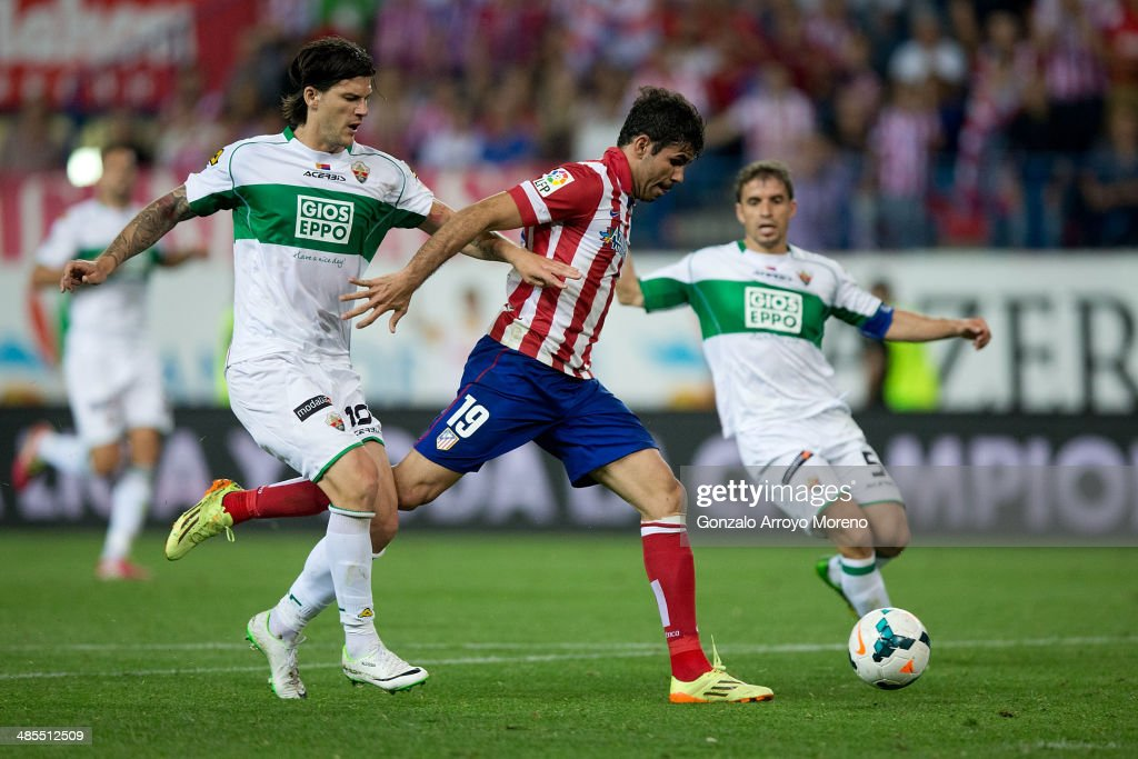 <a gi-track='captionPersonalityLinkClicked' href=/galleries/search?phrase=Cristian+Sapunaru&family=editorial&specificpeople=633831 ng-click='$event.stopPropagation()'>Cristian Sapunaru</a> (L) of Elche FC tackles Diego Costa (R) of Atletico de Madrid during the La Liga match between Club Atletico de Madrid and Elche FC at Vicente Calderon Stadium on April 18, 2014 in Madrid, Spain.