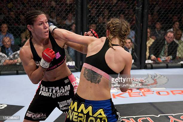 Cristiane 'Cyborg' Santos and Marloes Coenen trade punches during the Women's Featherweight Championship bout at the Strikeforce Miami event on...
