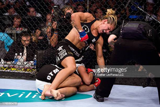 Cristiane 'Cyborg' Santos punches Gina Carano during the inaugural Strikeforce Women's Championship event at HP Pavilion on August 15 2009 in San...