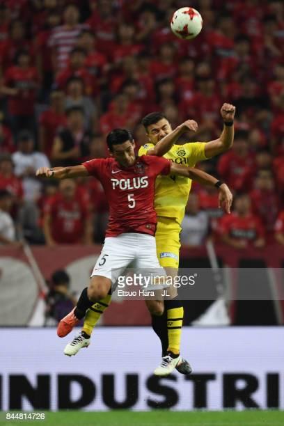 Cristiano of Kashiwa Reysol and Tomoaki Makino of Urawa Red Diamonds compete for the ball during the JLeague J1 match between Urawa Red Diamonds and...