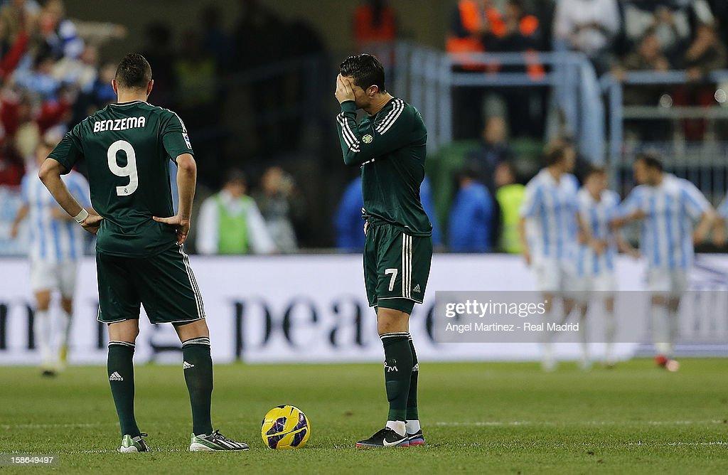 Cristiano Ronaldo (C) and Karim Benzema of Real Madrid react during the La Liga match between Malaga CF and Real Madrid at La Rosaleda Stadium on December 22, 2012 in Malaga, Spain.