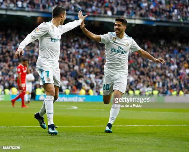 Cristiano Ronaldo and Marco Asensio of Real Madrid celebrate after scoring during the La Liga match between Real Madrid and Sevilla at Estadio...