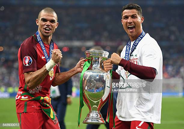 Cristiano Ronaldo and Pepe of Portugal pose for photographs holding the Henri Delaunay trophy to celebrate after their 10 win against France in the...
