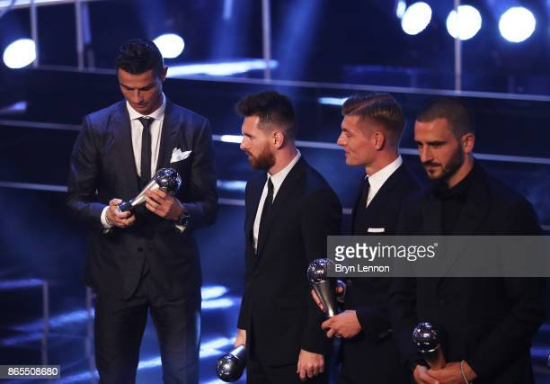 Cristiano Ronaldo looks at his trophy as Lionel Messi Toni Kroos and Leonardo Bonucci are named in The Fifa FifPro World XI during The Best FIFA...