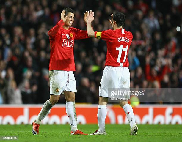 Cristiano Ronaldo of Manchester United celebrates with team mate Ryan Giggs at the end of the UEFA Champions League Round of Sixteen Second Leg match...