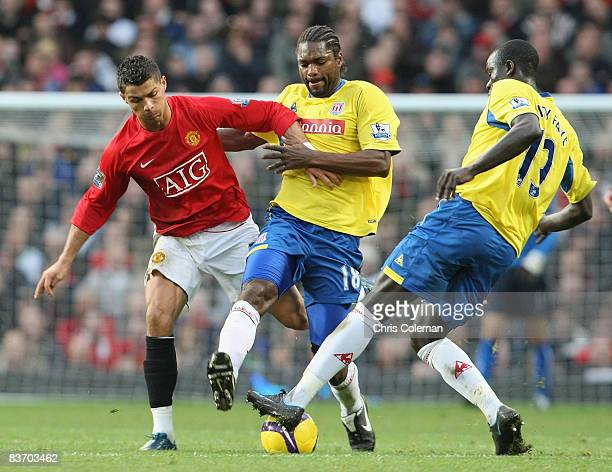 Cristiano Ronaldo of Manchester United clashes with Salif Diao and Amdy Faye of Stoke City during the Barclays Premier League match between...