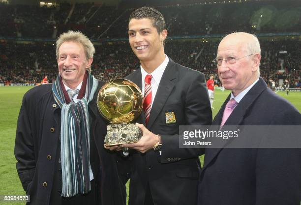 Cristiano Ronaldo of Manchester United is presented with the Ballon D'Or by Denis Law and Sir Bobby Charlton ahead of the UEFA Champions League Group...