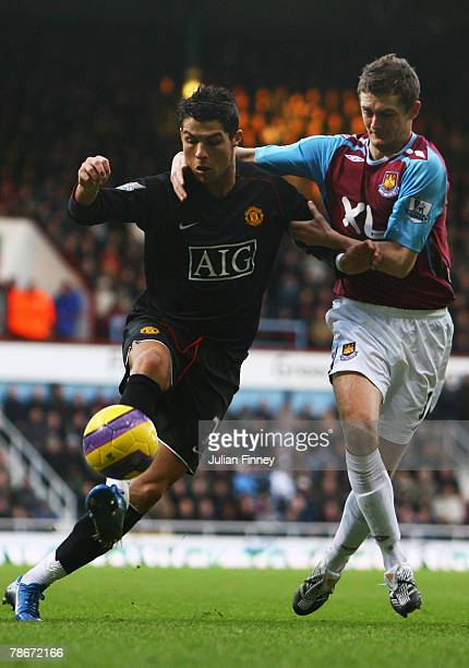 Cristiano Ronaldo of Manchester United tussles with George McCartney of West Ham United during the Barclays Premier League match between West Ham...