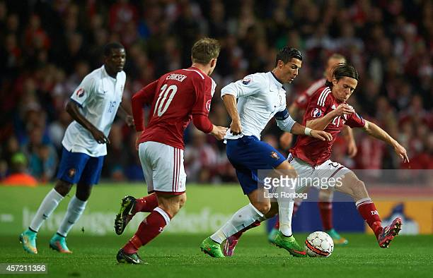 Cristiano Ronaldo of Portugal and Lasse Vibe of Denmark compete for the ball during the UEFA 2016 Group I Qualifier between Denmark and Portugal at...