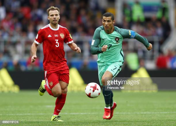 Cristiano Ronaldo of Portugal and Roman Shishkin of Russia compete for the ball during the FIFA Confederations Cup Russia 2017 Group A match between...