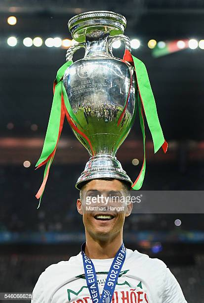 Cristiano Ronaldo of Portugal balances the Henri Delaunay trophy on his head to celebrate after his team's 10 win against France in the UEFA EURO...