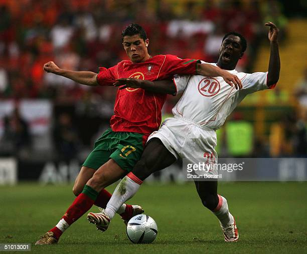 Cristiano Ronaldo of Portugal battles with Clarence Seedorf of Holland during the UEFA Euro 2004 Semi Final match between Portugal and Holland at the...