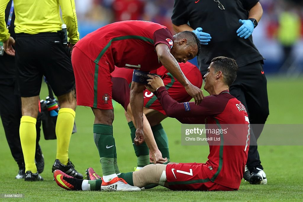 Cristiano Ronaldo of Portugal gives the captain's armband to teammate Nani before being carried off during the UEFA Euro 2016 Final match between...