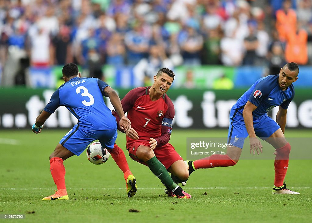 Cristiano Ronaldo of Portugal is challenged by Patrice Evra and Dimitri Payet of France during the UEFA EURO 2016 Final match between Portugal and...