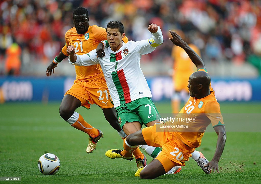Cristiano Ronaldo of Portugal is tackled by Guy Demel (R) and Emmanuel Eboue of Ivory Coast during the 2010 FIFA World Cup South Africa Group G match between Ivory Coast and Portugal at Nelson Mandela Bay Stadium on June 15, 2010 in Port Elizabeth, South Africa.