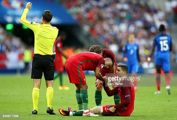 Cristiano Ronaldo of Portugal lies injured as teammates Adrien Silva and Nani check on him during the UEFA EURO 2016 Final match between Portugal and...