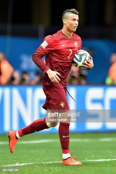Cristiano Ronaldo of Portugal picks up the ball from the net after their first goal for a quick restart during the 2014 FIFA World Cup Brazil Group G...