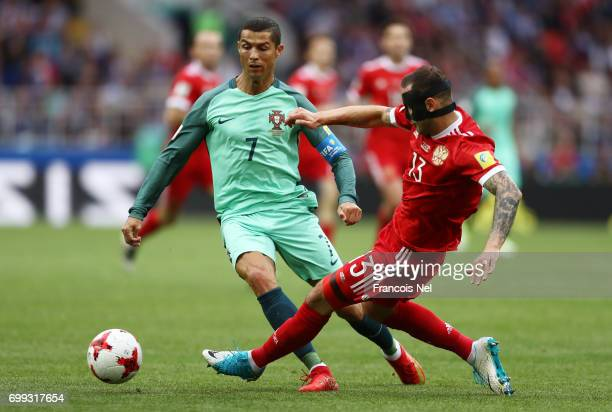 Cristiano Ronaldo of Portugal puts pressure on Fedor Kudriashov of Russia during the FIFA Confederations Cup Russia 2017 Group A match between Russia...