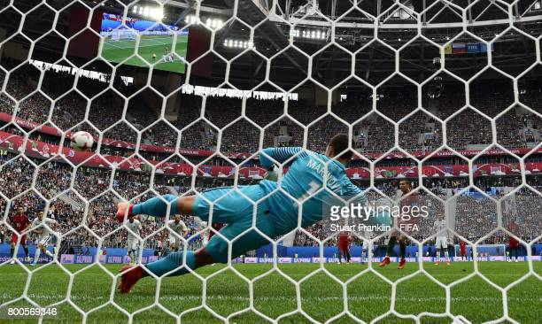 Cristiano Ronaldo of Portugal scores his sides first goal from the penalty spot past Stefan Marinovic of New Zealand during the FIFA Confederations...