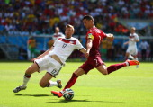 Cristiano Ronaldo of Portugal shoots against Per Mertesacker of Germany during the 2014 FIFA World Cup Brazil Group G match between Germany and...