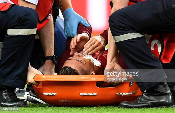 Cristiano Ronaldo of Portugal shows his emotion in the stretcher before being taken off the pitch during the UEFA EURO 2016 Final match between...