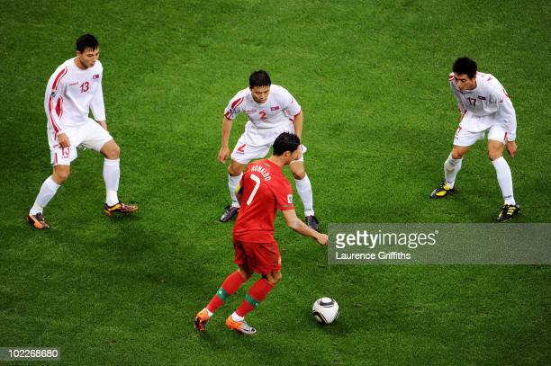 Cristiano Ronaldo of Portugal with the ball is surrounded by Pak CholJin Cha JongHyok and An YoungHak of North Korea during the 2010 FIFA World Cup...