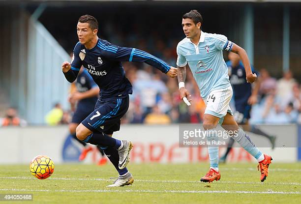 Cristiano Ronaldo of Real Madrid and Augusto Fernández of Celta de Vigo compete for the ball during the La Liga match between Celta de Vigo and Real...