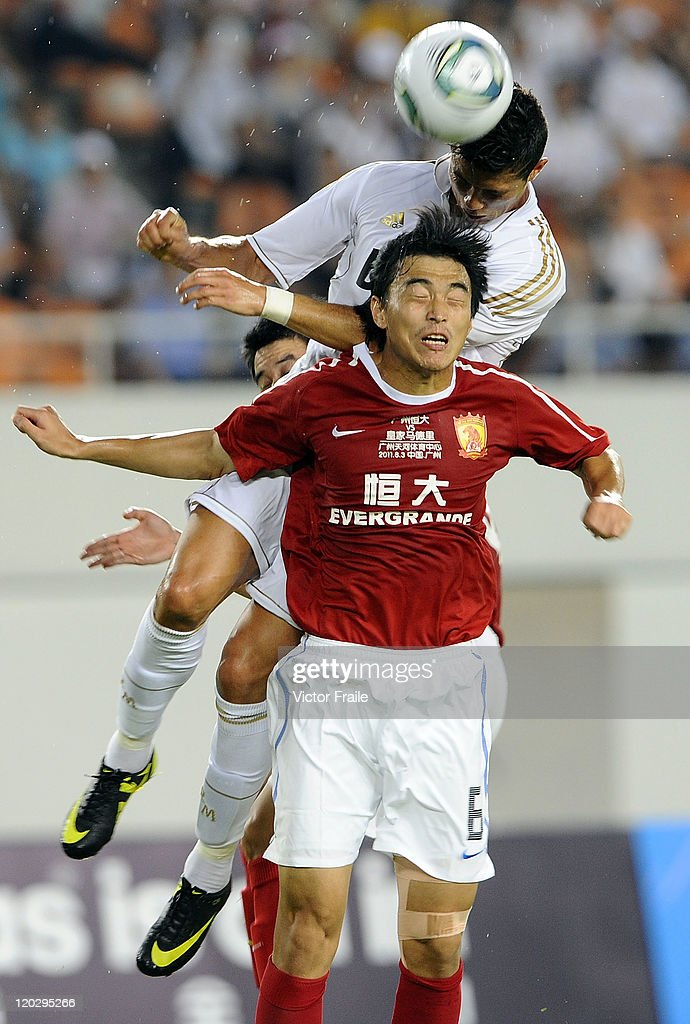 <a gi-track='captionPersonalityLinkClicked' href=/galleries/search?phrase=Cristiano+Ronaldo+-+Soccer+Player&family=editorial&specificpeople=162689 ng-click='$event.stopPropagation()'>Cristiano Ronaldo</a> of Real Madrid and Feng Xiaoting of Guangzhou Evergrande jumps for the ball during the pre-season friendly match between Guangzhou Evergrande and Real Madrid at the Tianhe Stadium on August 3, 2011 in Guangzhou, China.
