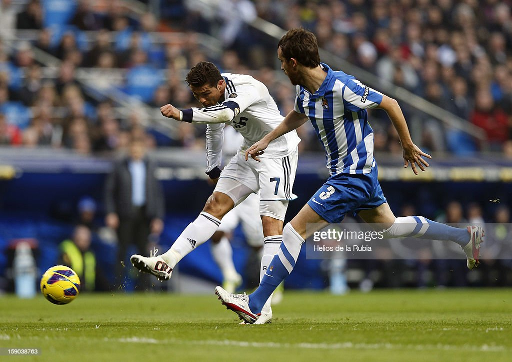 Cristiano Ronaldo (L) of Real Madrid and Mikel of Real Sociedad shoots the ball during the La Liga match between Real Madrid and Real Sociedad at Estadio Santiago Bernabeu on January 6, 2013 in Madrid, Spain.