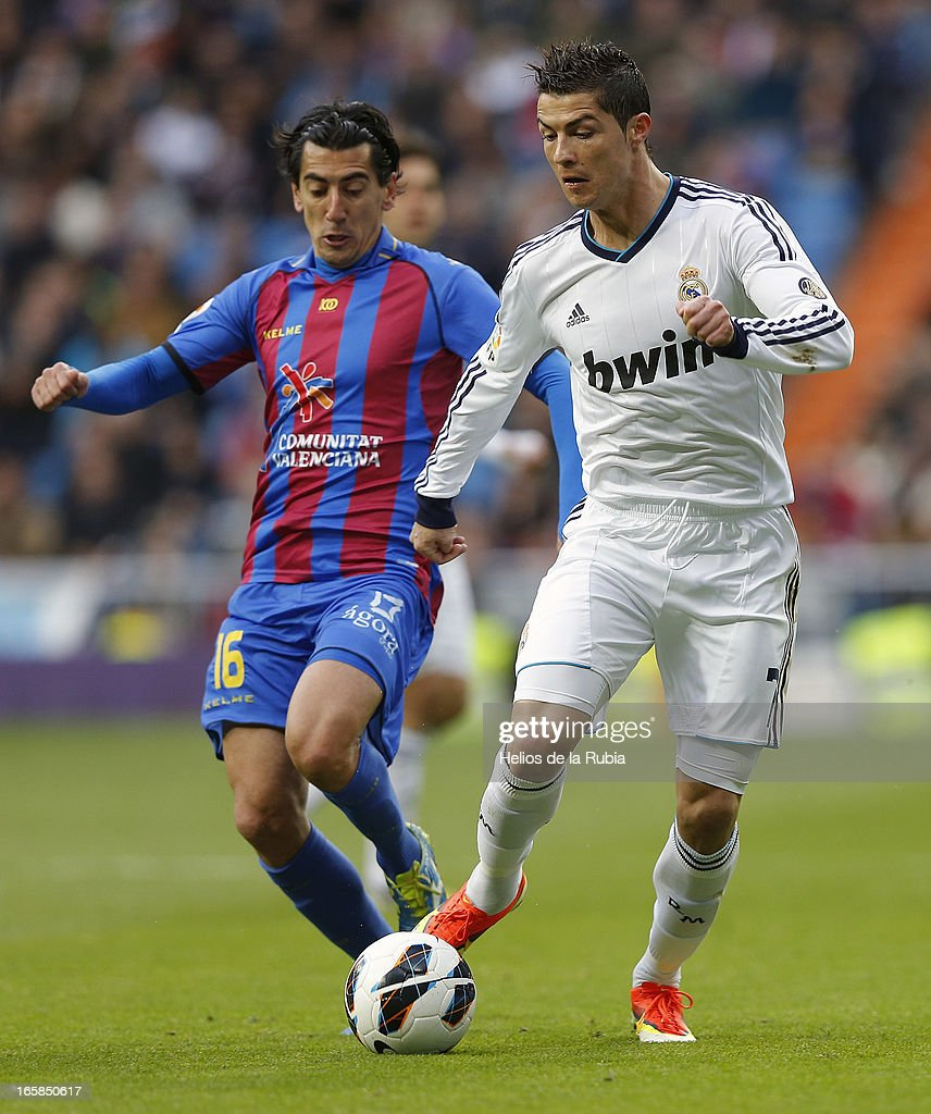 Cristiano Ronaldo (R) of Real Madrid and Pedro Rios of Levante compete for the ball during the La Liga match between Real Madrid and Levante at Estadio Santiago Bernabeu on April 6, 2013 in Madrid, Spain.