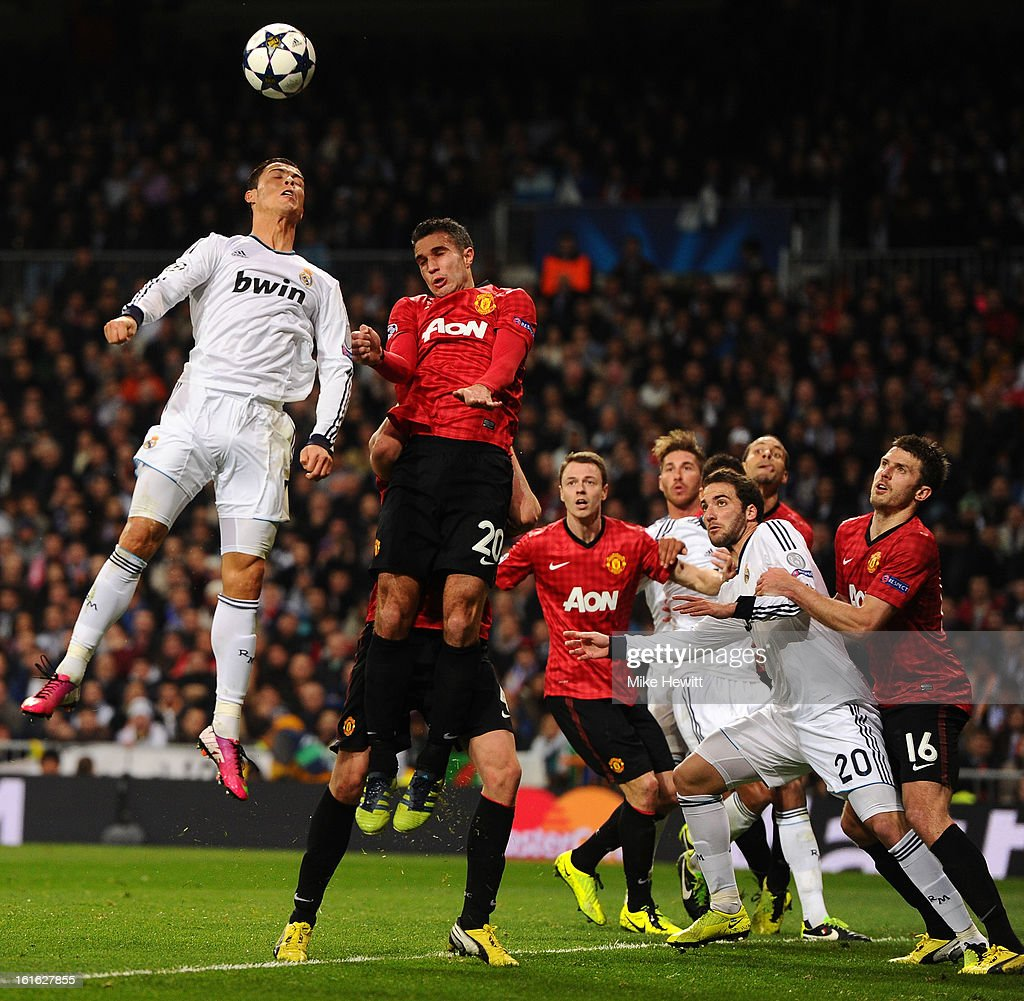 Cristiano Ronaldo of Real Madrid and Robin van Persie of Manchester United go up for a header during the UEFA Champions League Round of 16 first leg match between Real Madrid and Manchester United at Estadio Santiago Bernabeu on February 13, 2013 in Madrid, Spain.