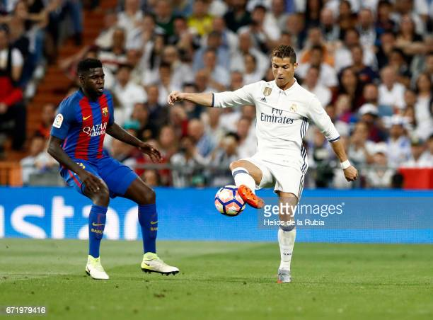 Cristiano Ronaldo of Real Madrid and Samuel Umtiti of Cf Barcelona compete for the ball during the La Liga match between Real Madrid CF and Barcelona...
