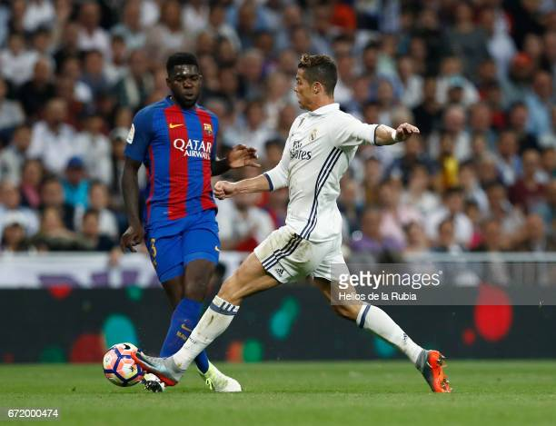Cristiano Ronaldo of Real Madrid and Samuel Umtiti of FC Barcelona compete for the ball during the La Liga match between Real Madrid CF and Barcelona...