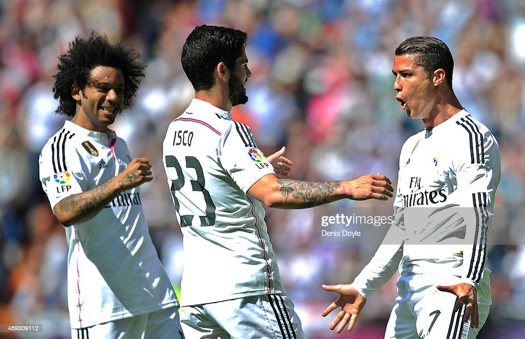 <a gi-track='captionPersonalityLinkClicked' href=/galleries/search?phrase=Cristiano+Ronaldo+-+Soccer+Player&family=editorial&specificpeople=162689 ng-click='$event.stopPropagation()'>Cristiano Ronaldo</a> of Real Madrid celebrates with <a gi-track='captionPersonalityLinkClicked' href=/galleries/search?phrase=Isco&family=editorial&specificpeople=5848609 ng-click='$event.stopPropagation()'>Isco</a> and <a gi-track='captionPersonalityLinkClicked' href=/galleries/search?phrase=Marcelo+-+Attacking+Left+Back+-+Born+1988&family=editorial&specificpeople=2136789 ng-click='$event.stopPropagation()'>Marcelo</a> after scoring Real's opening goal from a free kick during the La Liga match between Real Madrid and Eibar at Estadio Santiago Bernabeu on April 11, 2015 in Madrid, Spain.