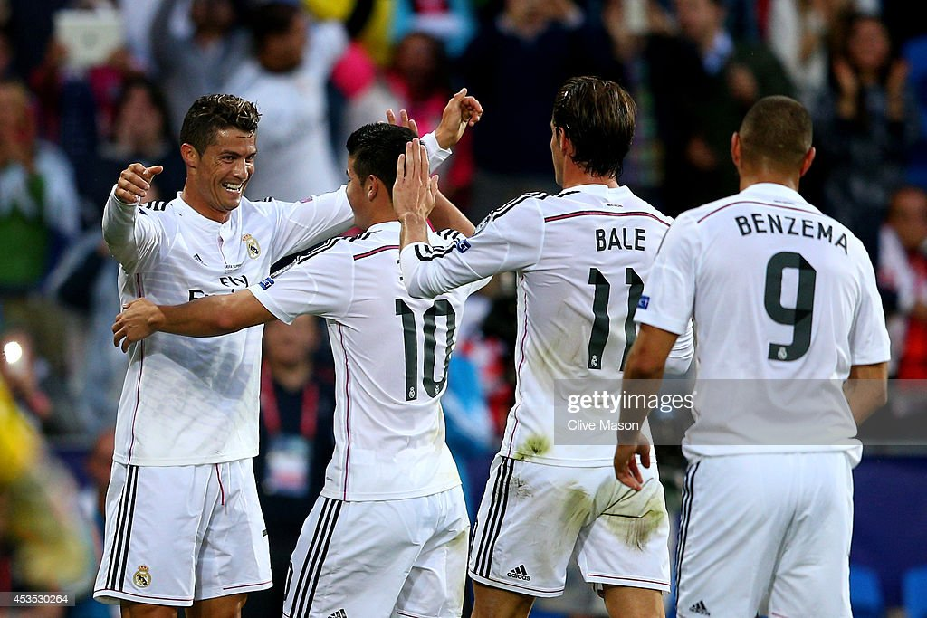 Cristiano Ronaldo of Real Madrid celebrates with teammates James Rodriguez, Gareth Bale and Karim Benzema after scoring the opening goal during the UEFA Super Cup between Real Madrid and Sevilla FC at Cardiff City Stadium on August 12, 2014 in Cardiff, Wales.