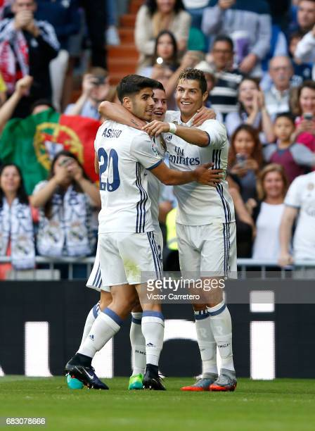 Cristiano Ronaldo of Real Madrid celebrates with teammates Marco Asensio and James Rodriguez after scoring his team's second goal during the La Liga...