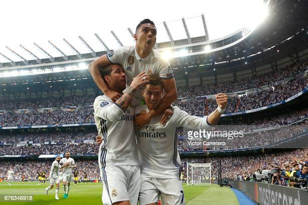 Cristiano Ronaldo of Real Madrid celebrates with teammates Sergio Ramos and Casemiro after scoring the opening goal during the UEFA Champions League...