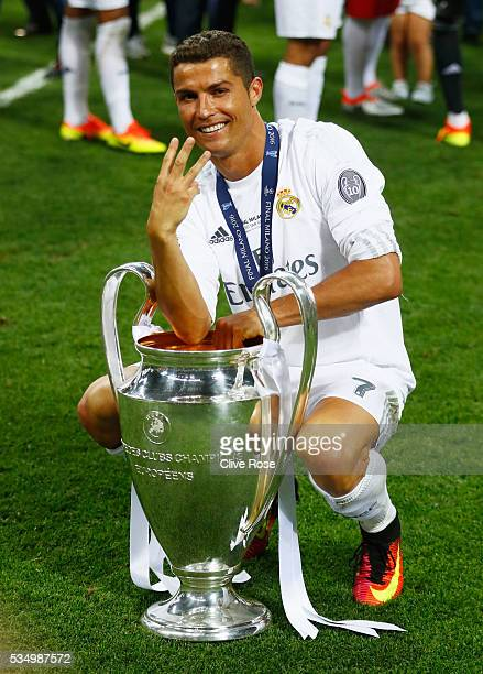 Cristiano Ronaldo of Real Madrid celebrates with the Champions League Trophy and gestures that it is his third time winning it after the UEFA...