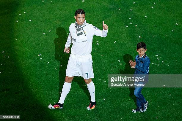 Cristiano Ronaldo of Real Madrid CF acknowledges the audience with his son Cristiano Ronaldo Jr during the celebration with their fans at Santiago...
