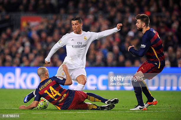 Cristiano Ronaldo of Real Madrid CF attempts to shoot under pressure from Javier Mascherano and Gerard Pique of FC Barcelona during the La Liga match...