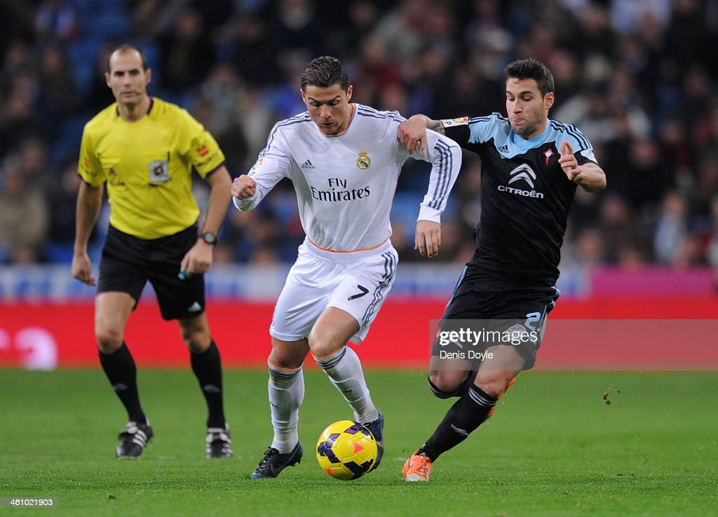 <a gi-track='captionPersonalityLinkClicked' href=/galleries/search?phrase=Cristiano+Ronaldo+-+Soccer+Player&family=editorial&specificpeople=162689 ng-click='$event.stopPropagation()'>Cristiano Ronaldo</a> (C) of Real Madrid CF battles for the ball against <a gi-track='captionPersonalityLinkClicked' href=/galleries/search?phrase=Hugo+Mallo&family=editorial&specificpeople=8007772 ng-click='$event.stopPropagation()'>Hugo Mallo</a> (R) of RC Celta de Vigo while referee Alfonso Alvarez looks on during the La Liga match between Real Madrid CF and RC Celta de Vigo at the Santiago Bernabeu stadium on January 6, 2014 in Madrid, Spain.