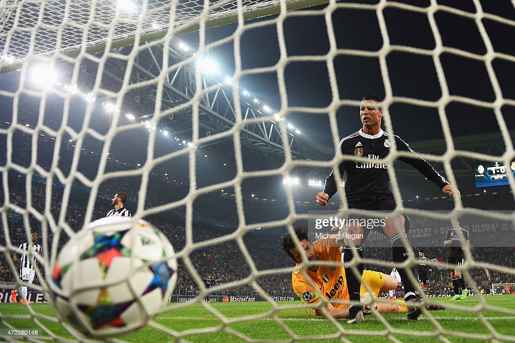 Cristiano Ronaldo of Real Madrid CF beats goalkeeper Gianluigi Buffon of Juventus to score their first and equalising goal during the UEFA Champions...