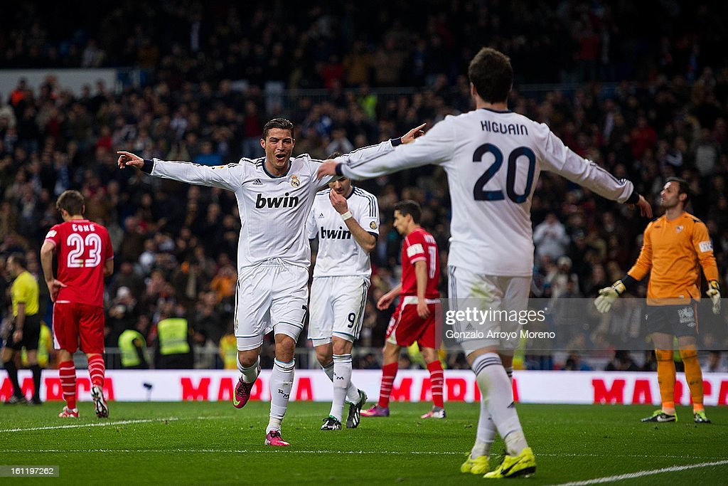<a gi-track='captionPersonalityLinkClicked' href=/galleries/search?phrase=Cristiano+Ronaldo+-+Soccer+Player&family=editorial&specificpeople=162689 ng-click='$event.stopPropagation()'>Cristiano Ronaldo</a> of Real Madrid CF (L) celebrates scoring their fourth goal with teammate <a gi-track='captionPersonalityLinkClicked' href=/galleries/search?phrase=Gonzalo+Higuain&family=editorial&specificpeople=651523 ng-click='$event.stopPropagation()'>Gonzalo Higuain</a> (R) during the La Liga match between Real Madrid CF and Sevilla FC at Estadio Santiago Bernabeu on February 9, 2013 in Madrid, Spain.