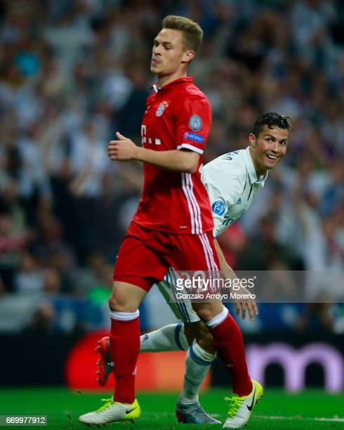 Cristiano Ronaldo of Real Madrid CF celebrates scoring their third goal behind Joshua Kimmich of Bayern Muenchen during the UEFA Champions League...